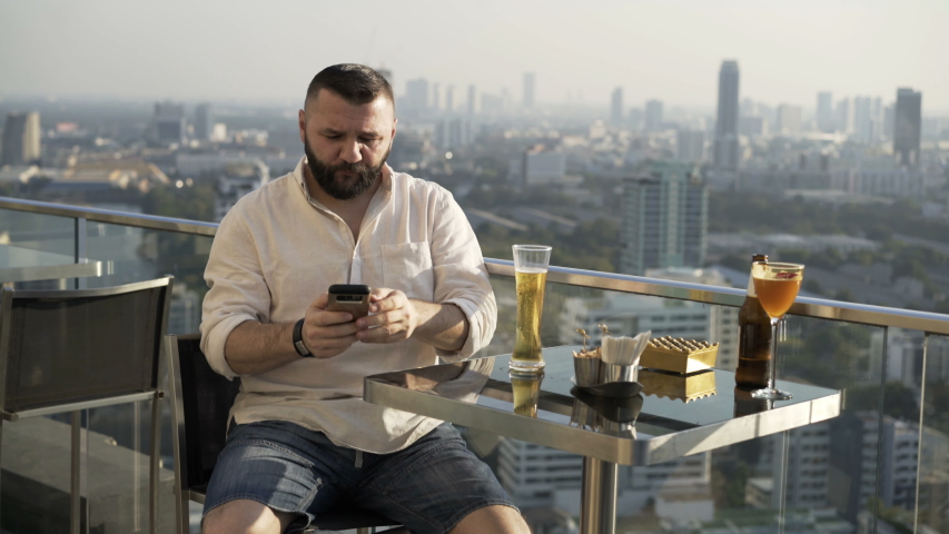Young man video chat on smartphone and drinking beer in skybar | Shutterstock HD Video #1055299319