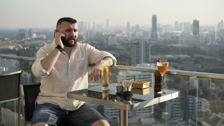 Young man talking on cellphone and drinking beer in skybar | Shutterstock HD Video #1055299322
