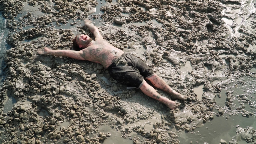 Funny Fat Man with Long Hair Lies and makes an Mud Angel. Overhead shot. | Shutterstock HD Video #1055304380