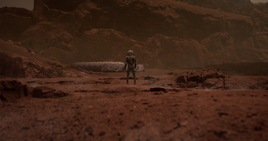 Back view of an astronaut looking on a space habitat colony from a distance. Mars colonization concept   Shutterstock HD Video #1055305574
