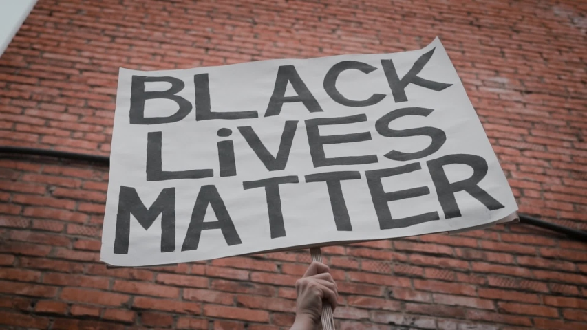 A Hand Holding up a Poster with the Slogan Black Lives Matter Against the background of a Brick Building. The Concept Of Stop Racism, No Racism. | Shutterstock HD Video #1055306861