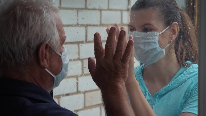 Woman in protective medical mask and illness old man touch their hands through glass window that separates them. Quarantine for coronavirus pandemic. Hope hand and support for recovery from covid-19 Royalty-Free Stock Footage #1055309036