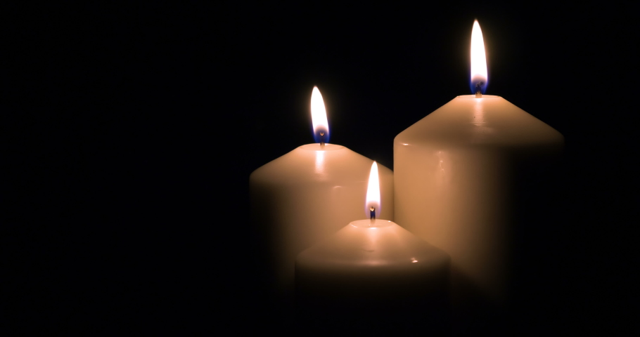 Three white candles burning on black background. 4k | Shutterstock HD Video #1055310659
