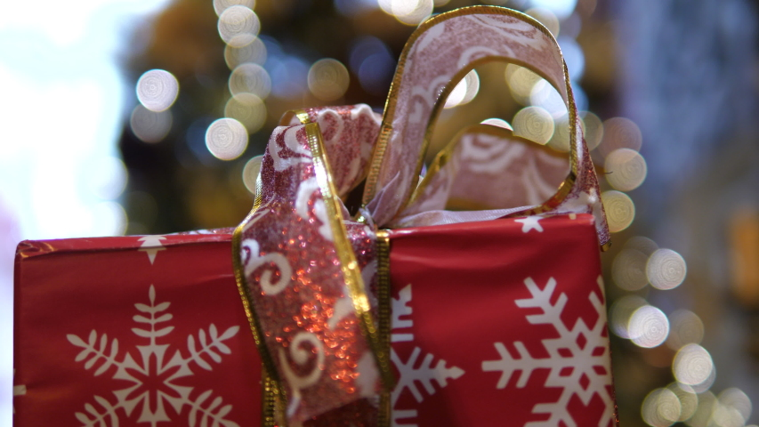 Gift Bag presents Christmas near Fireplace. Decorative Snowflakes wrapped box. Closed ribbon decorative bow. Isolated close-up. | Shutterstock HD Video #1055311232