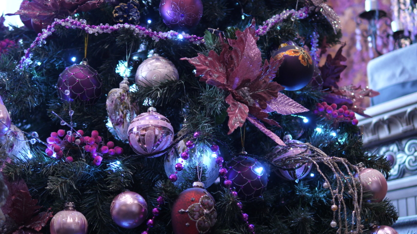 Luxury Christmas Tree decorations lights. Glitter sparkle pink flowers, purple, blue diamond balls and red decor berries. | Shutterstock HD Video #1055311259