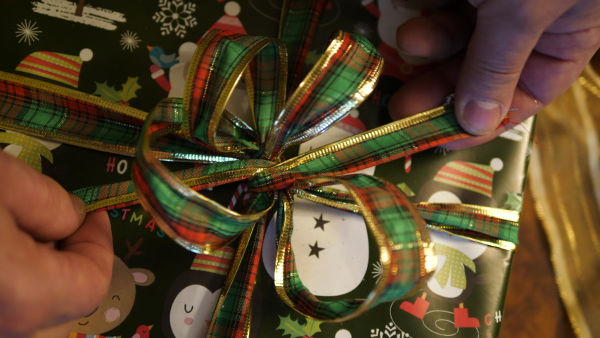 Hands Wrapp Christmas green gift Box. Closing with Ribbon and decor bow. Top close-up view. | Shutterstock HD Video #1055312069