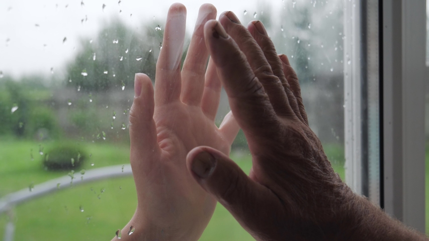 Woman and illness old man touch their palms through glass window that separates them. Quarantine for covid19 pandemic. Hope hand and support for recovery of coronavirus. Unrecognizable person, closeup | Shutterstock HD Video #1055314748