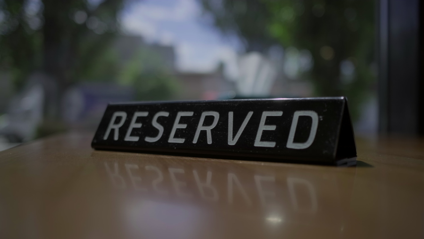 RESERVED sign placing on the cafe table with city view window. The table is reserved. Female hand put RESERVED tag on the table. | Shutterstock HD Video #1055315525