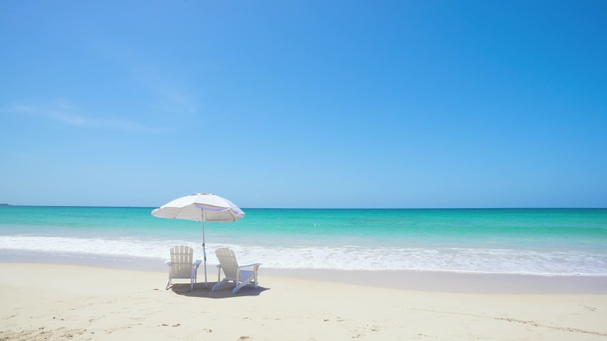 Mexico white sand beach and vibrant blue Pacific Ocean. Beach chairs and a parasol lie in the waves of the turquoise sea. Sunny vacation on the beach. Royalty-Free Stock Footage #1055315684