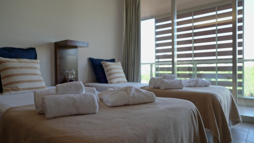 The modern bedroom of the hotel, houses with terry towels on the bed, overlooking the courtyard. Slow motion. | Shutterstock HD Video #1055316197