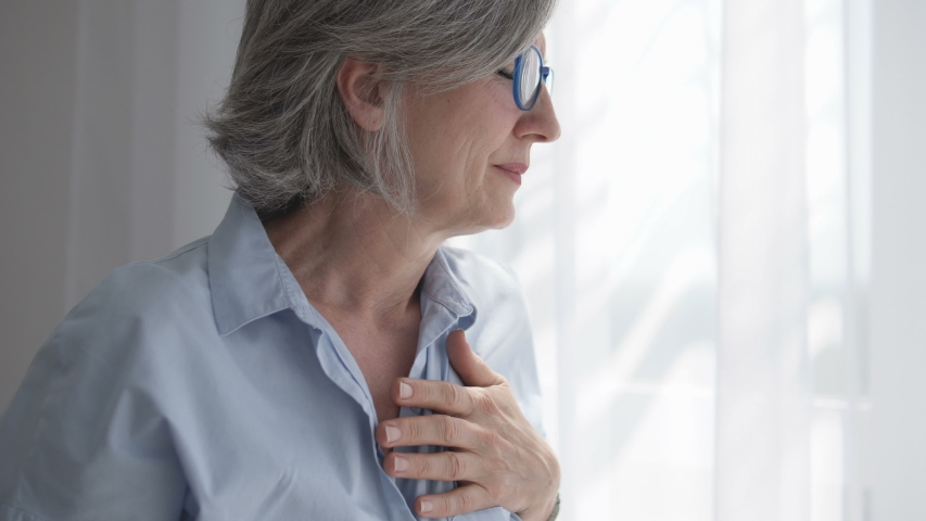 Adult woman holding hand on heart, feeling discomfort, risk of heart attack   Shutterstock HD Video #1055316290