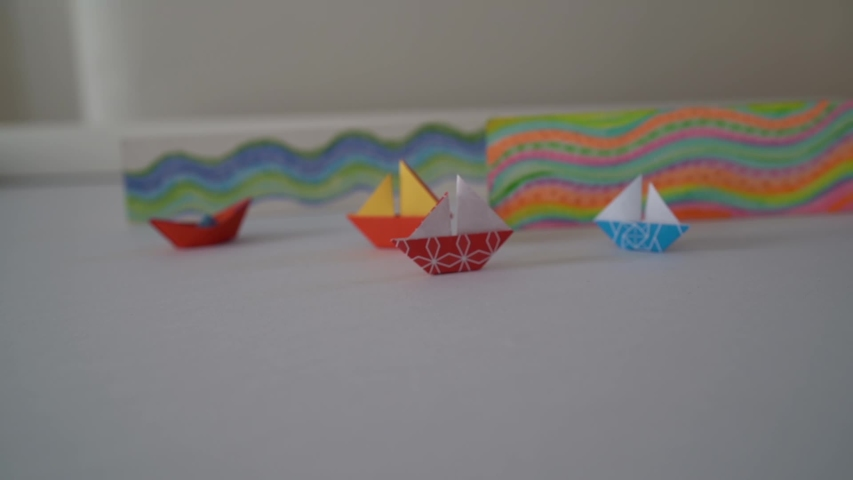 Paper boats of different colors, on white background | Shutterstock HD Video #1055316467