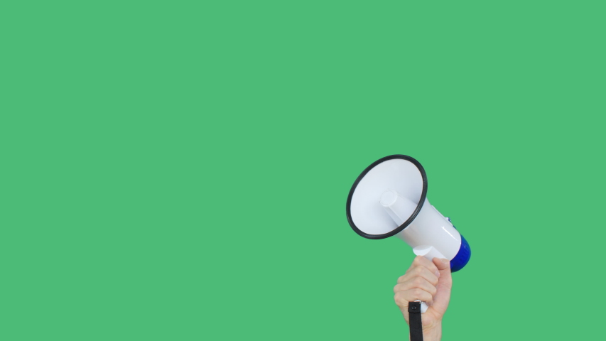 Megaphone close up rised in hand on green screen chroma key background. White loudspeaker for social performance in raised hand. Special announcement, advertisement or broadcast