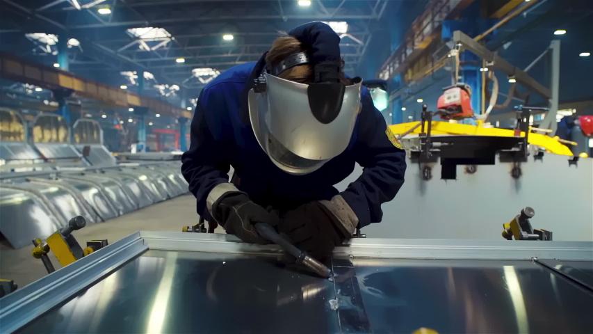 Welding man works at Train wagon manufacture. Railcar manufacturer. Welder Soldering the Steel Structure wears protective helmet. Bright Blue Green Light, Sparks, Automated Welding Machine, Welder | Shutterstock HD Video #1055316752