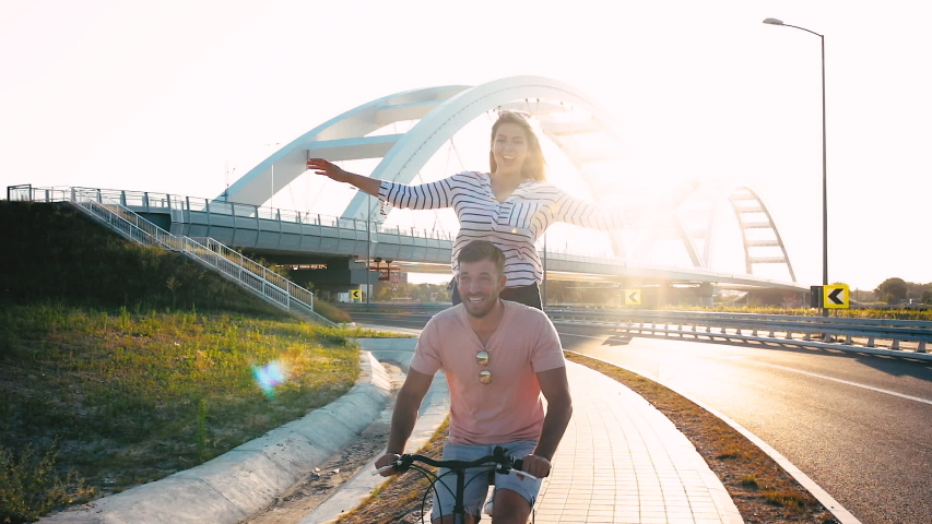 Cheerful young couple having fun riding on bicycle on summer day. | Shutterstock HD Video #1055317313