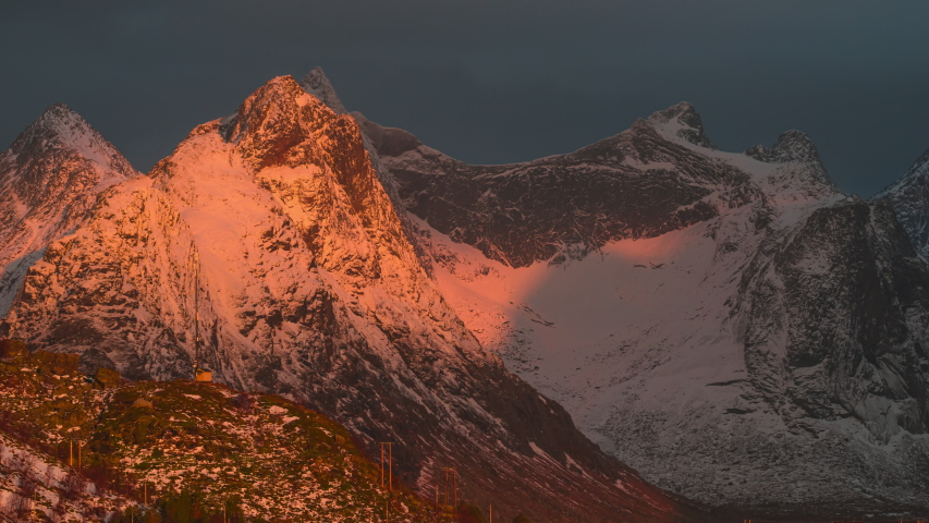 4K, 30fps, 10bit, YUV422 timelapse of  Reine Village with the sun shines on snow mountains in sunrise, Hamnoy, Lofoten Islands, Norway | Shutterstock HD Video #1055317322