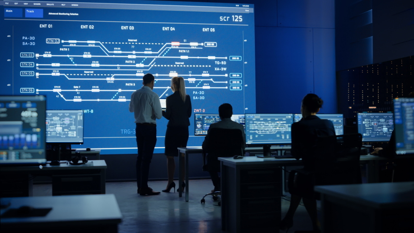 Telecommunications Company System Control and Monitoring Room with Diverse Multicultural Team of Professionals Working on Personal Computers. Big Screen Display Showing Infrastructure. Back View Royalty-Free Stock Footage #1055317487