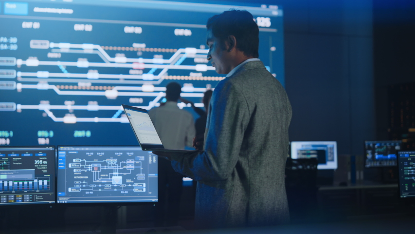 Handsome Confident Male Project Manager works on a Laptop Standing in Telecommunications System Control Room. In Background Big Screen Showing Infographics of Infrastructure, Charts, System Analysis Royalty-Free Stock Footage #1055317499