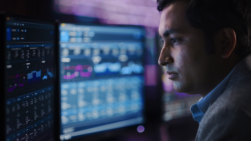 Confident Handsome Man Looks at Computer Monitor, Screen Showing Data, Infographics, Information, Statistics, Numbers. Businessman Working on Computer in the Office Royalty-Free Stock Footage #1055317535