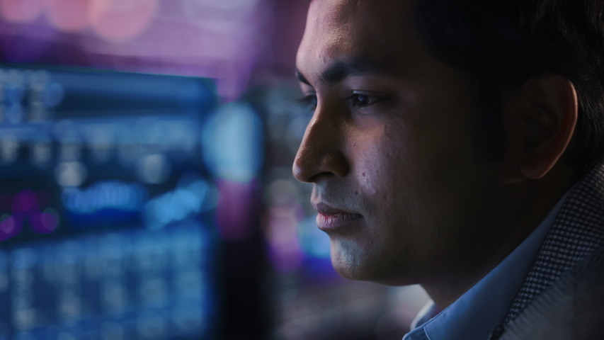 Confident Handsome Man Looks at Monitor Screen with Camera Moving to Computer Screen Showing Data, Infographics, Information, Statistics, Numbers. Businessman Working on Computer in the Office Royalty-Free Stock Footage #1055317544