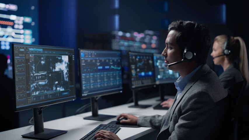 Confident Male Cyber Security Specialist Wearing Headset Works on Personal Computer Showing Footage of Drone Surveillance Tracking of a Vehicle. Big Monitoring Room with Professional People Working Royalty-Free Stock Footage #1055317556