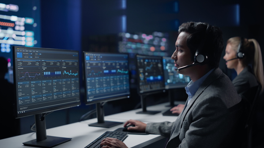 Team of Professional Traders Talking into Headsets Work on Computers with Screen Showing Finance Statistics, Charts Strategy, Stock, Telemarketing. Big Stock Firm Monitoring Room full of Specialists Royalty-Free Stock Footage #1055317559