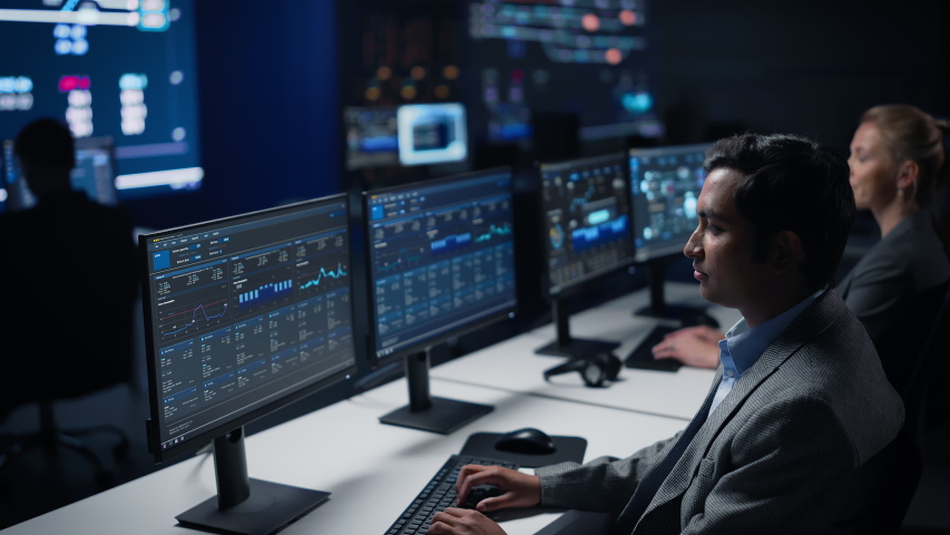Confident Male Data Scientist Works on Personal Computer in Big Infrastructure Control Room. Stock Market Woman Specialist Uses Computer Showing Graphs, Charts, Information. Monitoring Room Team Royalty-Free Stock Footage #1055317571