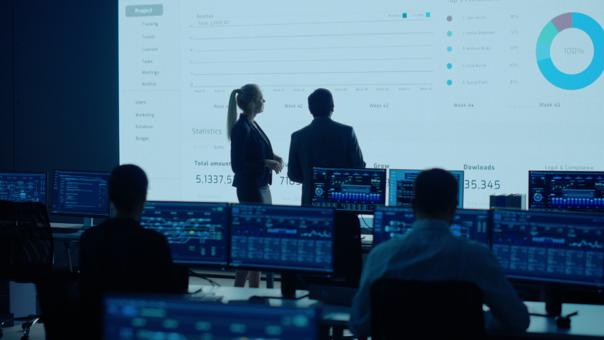 Project Leader and Chief Executive Discuss Data Shown on Big Display. Screens Show Infographics, Charts, Finance Analysis, Stock Market, Growth.Telecommunications Control Room Working Professionals