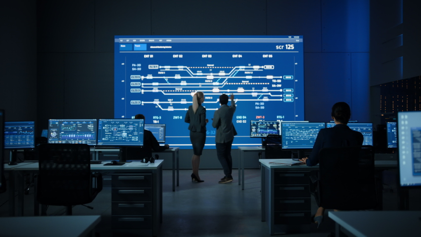 Project Manager and Computer Science Engineer Talking while Using Big Screen Display Showing Infrastructure Infographics, Data. Telecommunications Company System Control and Monitoring Room. Zoom out Royalty-Free Stock Footage #1055317613