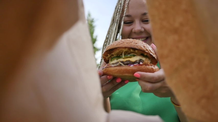 Pretty young woman is eating appetizing hamburger on the street. Close-up | Shutterstock HD Video #1055317952