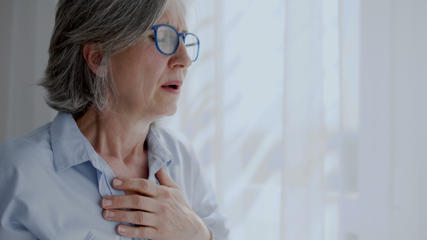 Mature woman hardly breathing and feeling pain in chest, heart attack, emergency | Shutterstock HD Video #1055318471