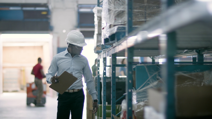 eCommerce warehouse manager inspects inventory at shipping centre. Business is booming online. Back to work. Shot in 4k. Royalty-Free Stock Footage #1055319635