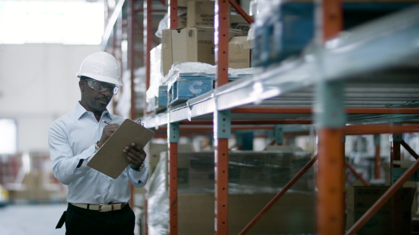 eCommerce warehouse manager inspects inventory at shipping centre. Business is booming online. Back to work. Shot in 4k. Royalty-Free Stock Footage #1055319638