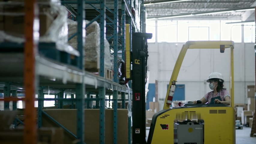 Forklift moving inventory's  around for online delivery and shipping. Business is back to work. Shot in 4k.  Royalty-Free Stock Footage #1055319719