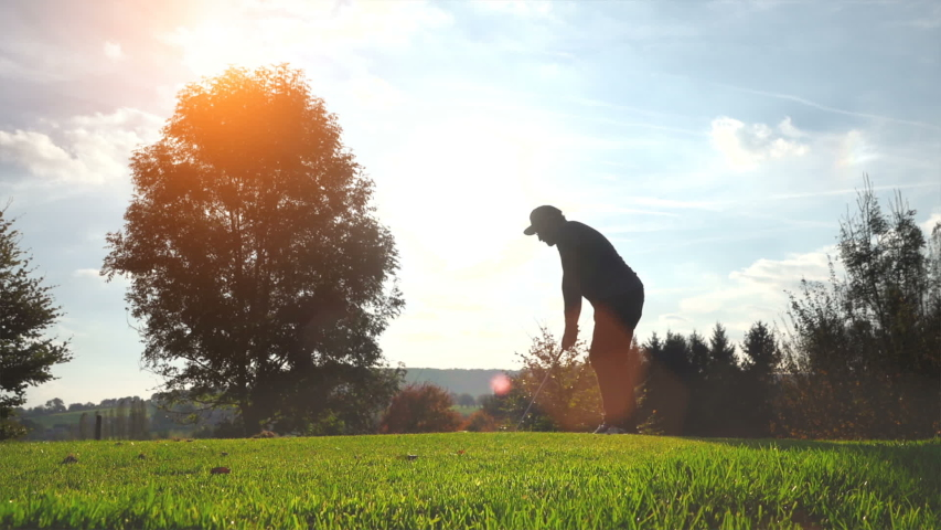 Golf Player plays golf on a beautiful summer morning. wide angle Lens flare Back lite ultra slow motion shot