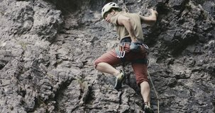 Climber reaches clips secures rope in carabiner puts his hand into chalk bag climbing on stone rock wall wearing a helmet outdoors adventure sport