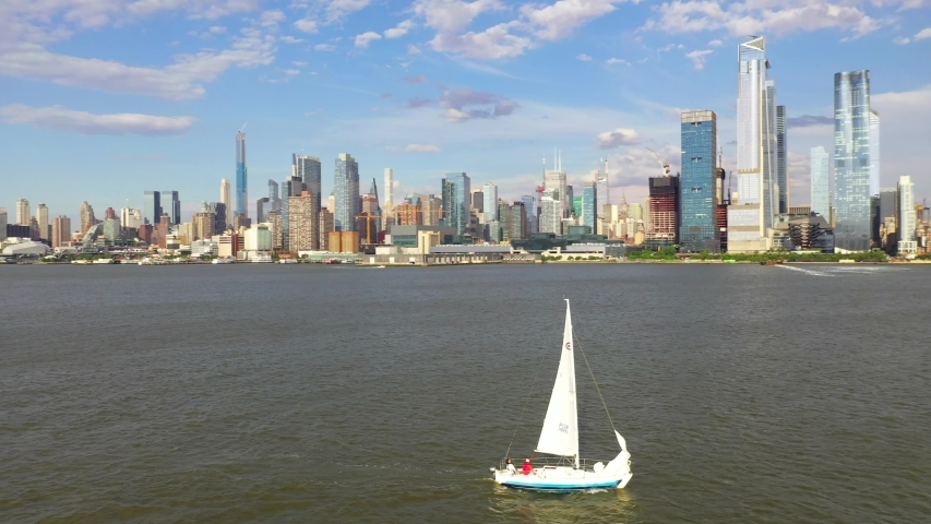 Aerial view of a sailboat going through the Hudson River.  A beautiful backdrop of New York City is in the backdrop | Shutterstock HD Video #1055323400