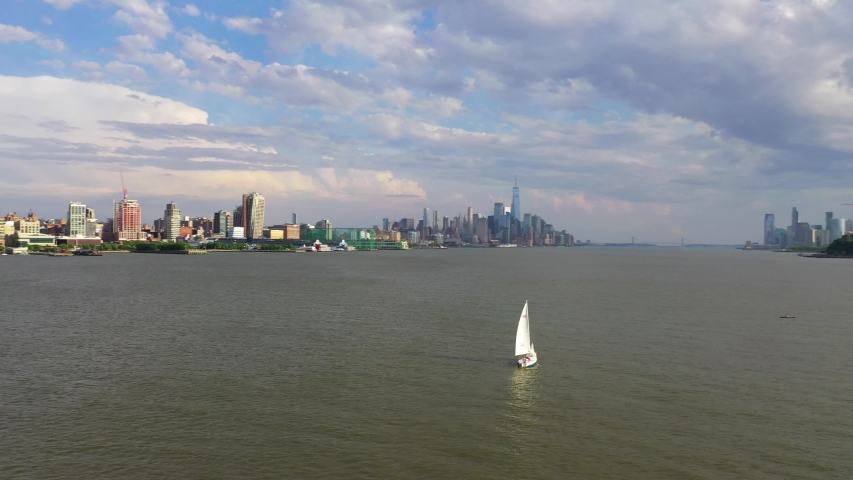 Aerial view of a sailboat going through the Hudson River.  A beautiful backdrop of New York City is in the backdrop | Shutterstock HD Video #1055323403