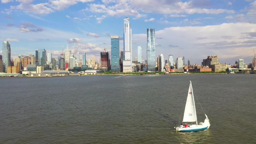 Aerial view of a sailboat going through the Hudson River.  A beautiful backdrop of New York City is in the backdrop | Shutterstock HD Video #1055323409