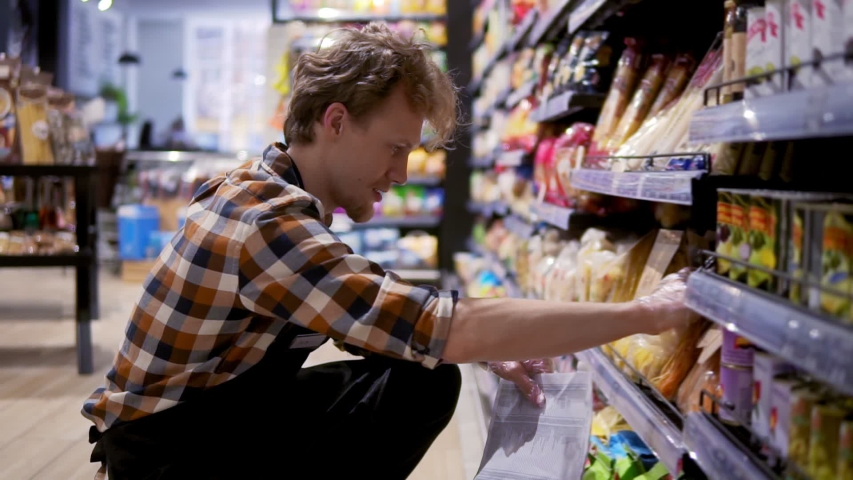 Busystore clerk working at the supermarket he is resorting items on a shelf, writing down the lack of products, sorting items on a lower shelf   Shutterstock HD Video #1055323670