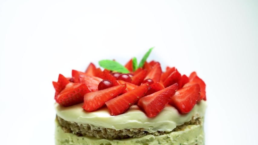 Delicious cake covered in strawberries and mint decorated with cranberries rotates isolated on white background. Sweet treat. Not proper diet good nutrition food | Shutterstock HD Video #1055323781