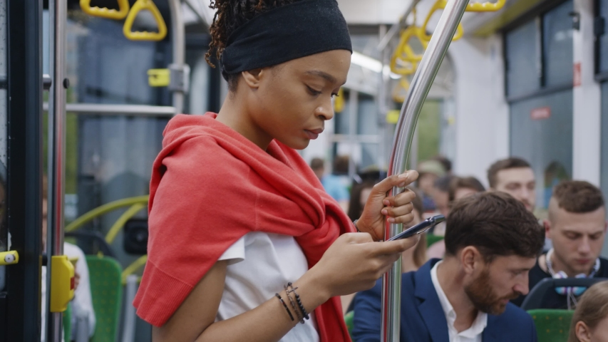Young afro-american black girl using mobile phone internet social network application while traveling by bus to city center. Citizens. Diverse people. Public transport.