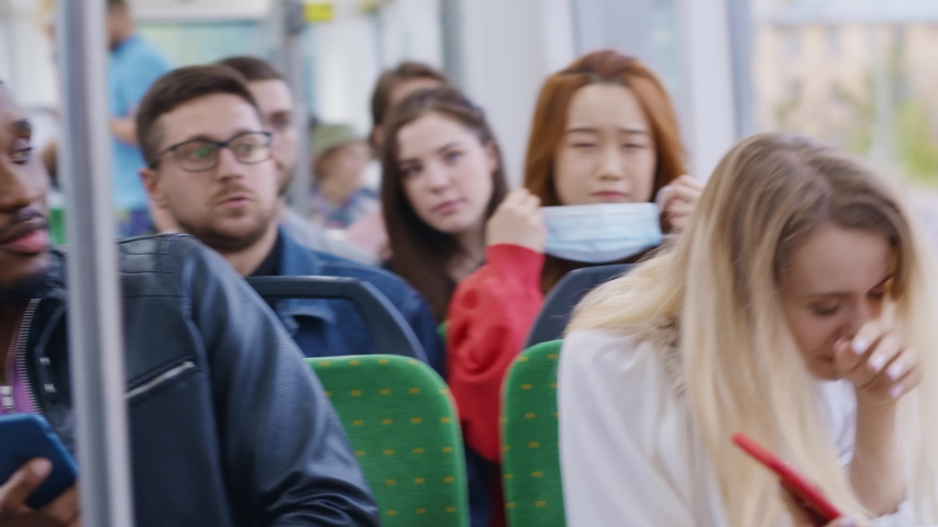 Sick blonde woman with cold sneezing allergy in the tram. Frightened people hurry to wear masks and leaving. Health care, public safety. Transportation. Coronavirus.