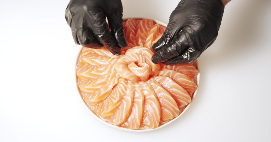 Close-up of cook hands in gloves laying slices of fresh salmon on daikon salad on a plate | Shutterstock HD Video #1055327672