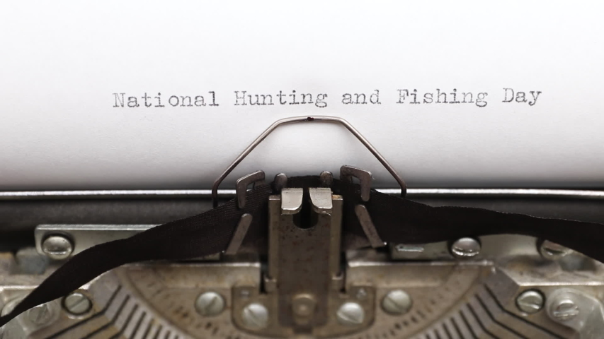 Typing a phrase National Hunting and Fishing Day on a vintage typewriter close-up. concept of festive banner for national holiday | Shutterstock HD Video #1055327675