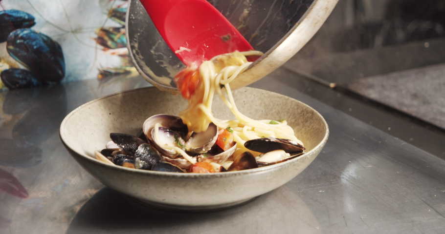 Closeup male cook hands in gloves serving delicious italian carbonara pasta with mussels and vegetables in the kitchen | Shutterstock HD Video #1055328467