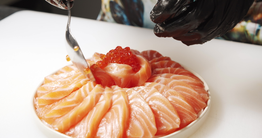 Close up of male cook hands in gloves decorating dish of daikon salad and slices of salmon with red caviar in the kitchen | Shutterstock HD Video #1055329085