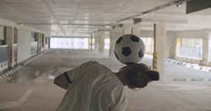 Teenager girl football soccer player practicing tricks, kicks and moves with ball inside empty covered parking garage. Urban city lifestyle outdoors concepte. 4K UHD slow motion RAW graded footage
