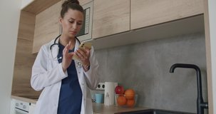 Lunch break in a medical facility. Female doctor in lab coat standing in clinic and scrolling on smartphone screen while kitchen in background. 4k raw video footage slow motion