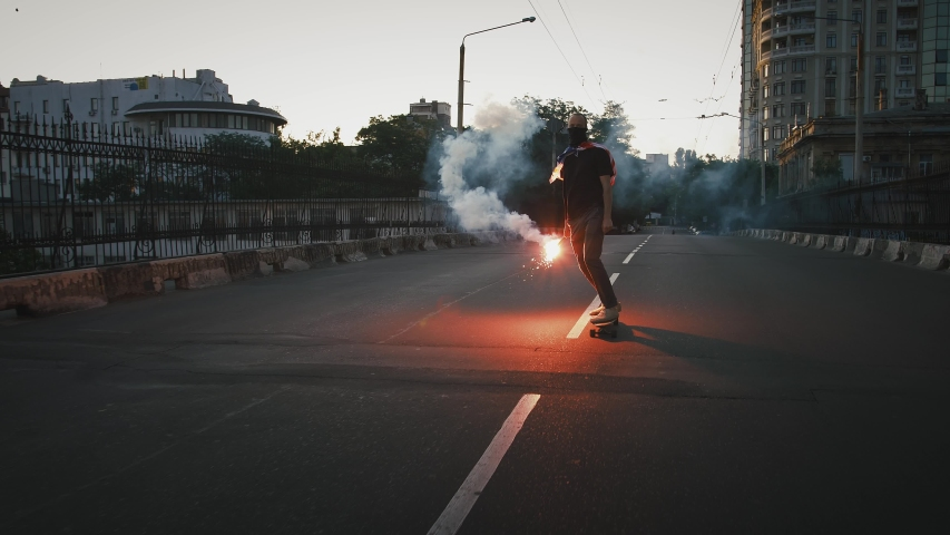 Young male in bandana on face and flag of USA tied on chest is skateboarding along deserted street with glowing red signal flare in hand. Slow motion